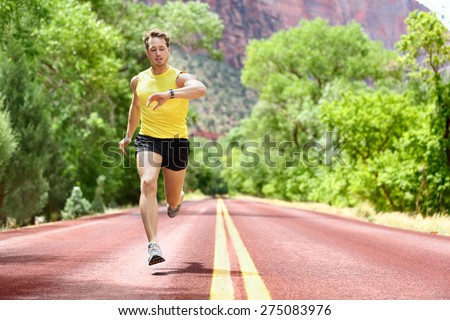 Running man sprinting looking at heart rate monitor smartwatch on run. Man jogging outside looking at his sports smart watch during workout training for marathon. Fit male fitness model in his 20s. - stock photo