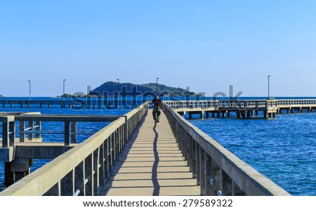 running man with nice view of long cement bridge walk way run on the blue sea with black shadow in blue sky sunshine day