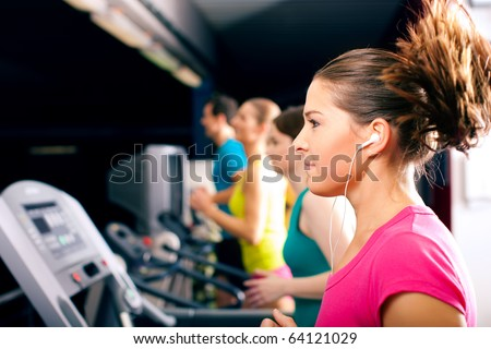 Running on treadmill in gym - group of women and men exercising to gain more fitness, the woman in front wears earplugs and enjoys music - stock photo