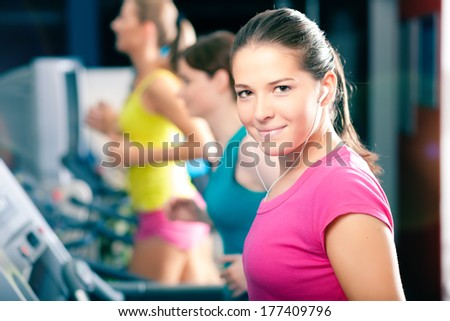 Running on treadmill in gym - group of women exercising to gain more fitness - stock photo