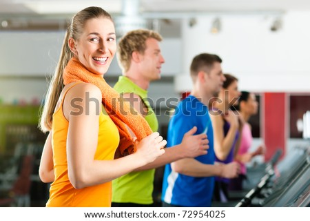 Running on treadmill in gym or fitness club - group of women and men exercising to gain more fitness - stock photo