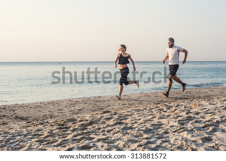 Running people - woman and man athlete runners jogging on beach. Fit young fitness couple exercising healthy lifestyle outdoors during sunrise or sunset - stock photo