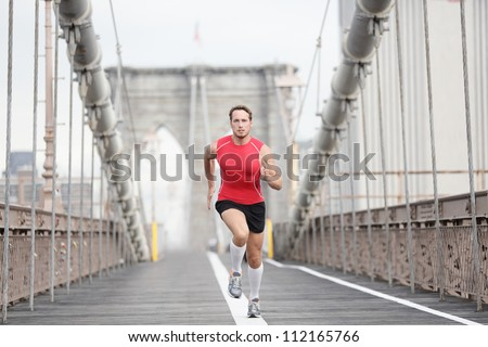 Running runner man sprinting at speed. Male athlete training alone in full body wearing red compression top and socks during run on Brooklyn Bridge, New York City, USA. - stock photo