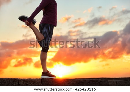 Running runner woman stretching leg muscle preparing for sunset trail run in outdoor summer nature. Female athlete lower body crop of feet doing legs stretches getting ready for cardio warmup.