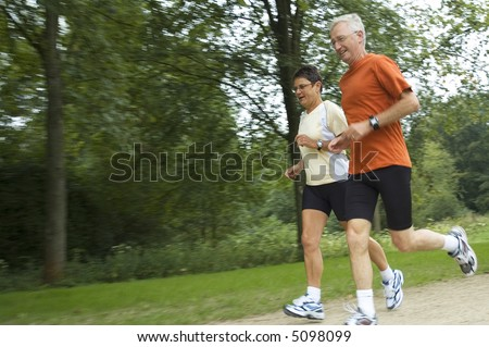 Running senior couple with motion in the picture. Focus is on the woman. - stock photo