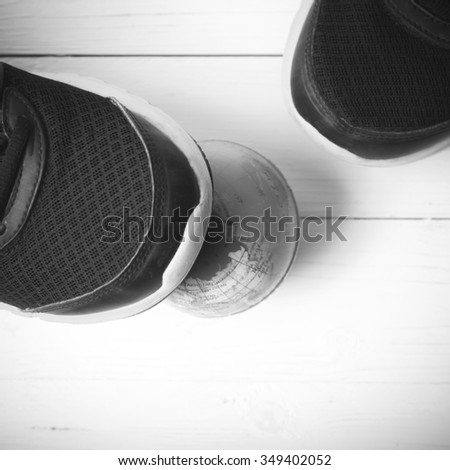 running shoes and earth ball on white wood table concept world healthy black and white tone color style