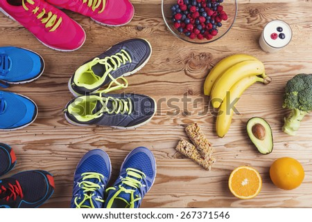 Running shoes and healthy food composition on a wooden table background - stock photo