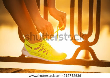 Running shoes. Barefoot running shoes closeup. Female athlete tying laces for jogging on road in minimalistic barefoot running shoes. Runner getting ready for training. Sport lifestyle. - stock photo