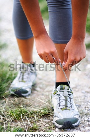 Running shoes being tied by woman getting ready for jogging.Shallow depth of field, focus on hands. - stock photo