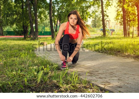 Running shoes - closeup of woman tying shoe laces. Female sport fitness runner getting ready for jogging outdoors on forest path in spring or summer. - stock photo