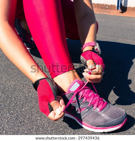 Running shoes-closeup woman tying shoe laces. Female sport fitness runner getting ready for jogging outdoors on forest path in spring or summer. Street runner getting ready for training. Pink leggins. - stock photo