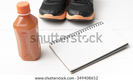running shoes,orange juice and notepad on white wood background