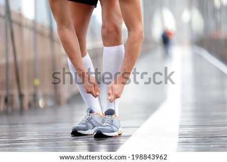 Running shoes - Runner man tying laces, New York City on Brooklyn Bridge. Male athlete runner and feet closeup. Fitness model wearing compression socks. - stock photo