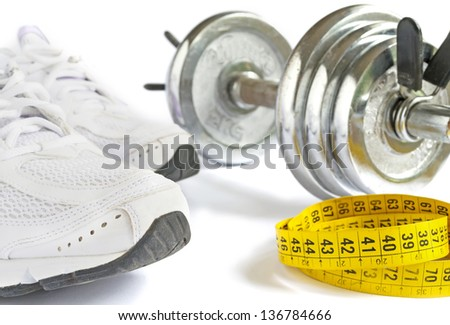 running shoes, tape and metal dumbbell on white background - stock photo