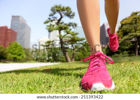 Running shoes - woman runner jogging staying fit in Tokyo Park, Japan. Closeup of pink trainers in green grass in summer park near the Imperial Palace and Ginza district downtown. - stock photo