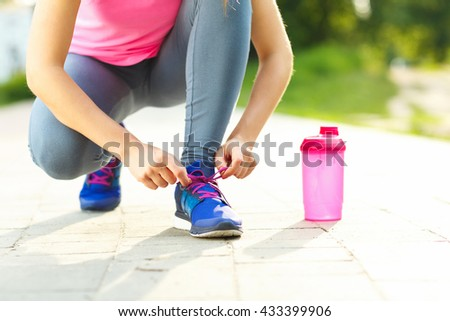 Running shoes - woman tying shoe laces. Closeup of female sport fitness runner getting ready for jogging outdoors in summer - stock photo