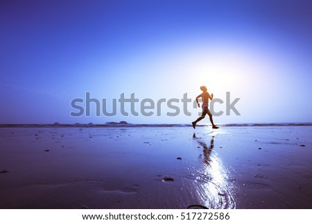 running, silhouette of runner on the beach at sunset, blue background with copyspace and reflection