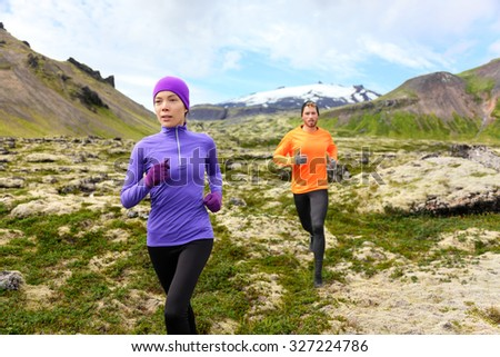 Running sport. Runners on cross country trail outdoors working out for marathon. Fit young fitness model man and asian woman training together outside in mountain nature. - stock photo