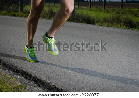 Running sport shoes outdoors in action on country road. Male shoes on young man training. Slight motion blur, focus on back running shoe. - stock photo