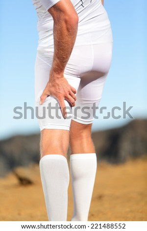 Running sports injury. Pulled hamstring muscle, muscle strain or muscle cramp in back thigh leg of man running outdoors. - stock photo