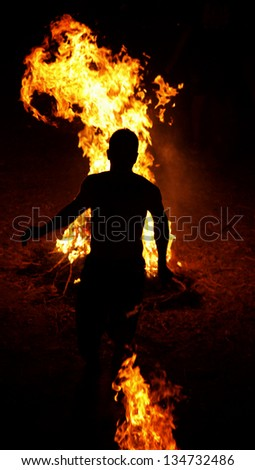 Running through flames.Traditional celebration of summer solstice on the island of Kalymnos - Greece. Inhabitants of the village gather and run several times through flames during the evening. - stock photo