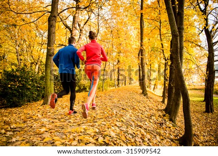 Running together - young couple jogging in autumn park, rear view