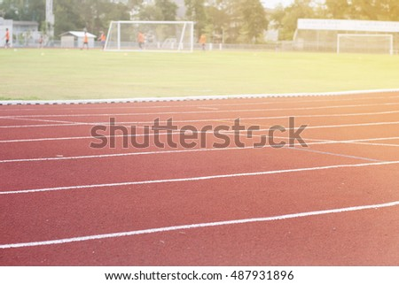 Running track around the football field with the evening sun