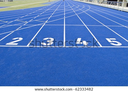 Running track in outdoor stadium with blue asphalt and white markings - stock photo