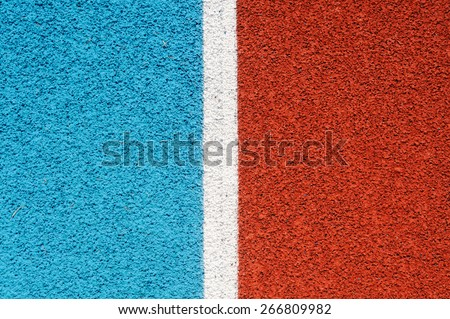 Running track made from red and blue granule rubber split by white line - stock photo