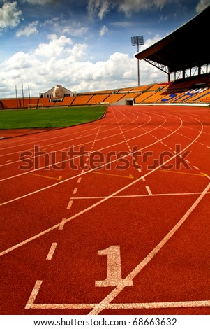 Running track number  in front of tracks and stadium with blue sky and white cloud. - stock photo