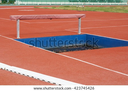 Running track with hurdle and puddle - stock photo