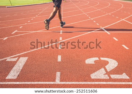 Running track with number and legs of runner - stock photo