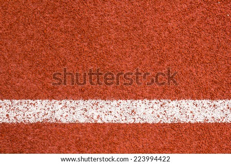 Running track with white striped on redbrick color background. - stock photo