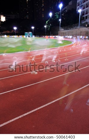 Running tracks in a stadium, with human running blur - stock photo