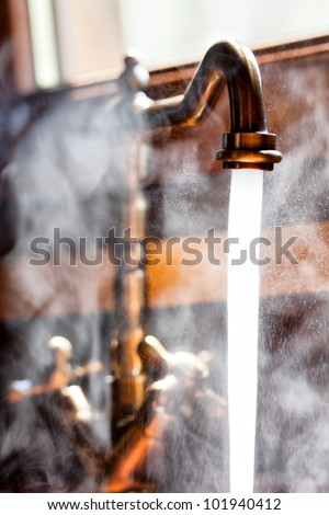 Running vintage faucet with hot water. Close-up view - stock photo