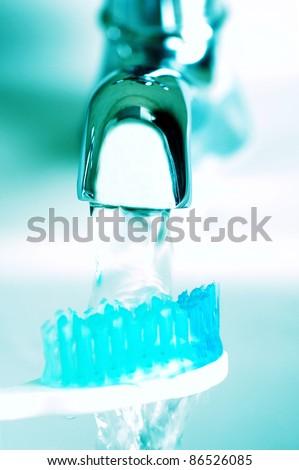 Running water and toothbrush - stock photo