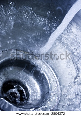 Running water drains down a stainless steel sink - stock photo