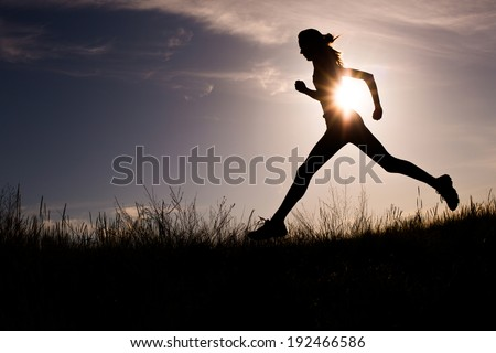 Running woman at beautiful sunset sky. Summer sport and freedom concept. Athlete training on dusk - stock photo