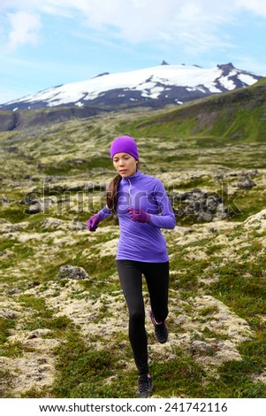 Running woman athlete exercising trail runner. Fit female sport fitness model training and jogging outdoors in beautiful mountain nature landscape by Snaefellsjokull, Snaefellsnes, Iceland. - stock photo