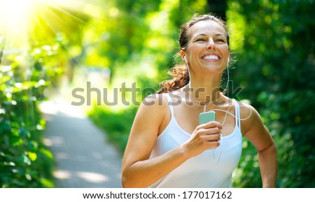 Running woman. Female Runner Jogging during Outdoor Workout in a Park. Beautiful fit Girl. Fitness model outdoors. Weight Loss. Healthy lifestyle. Morning - stock photo