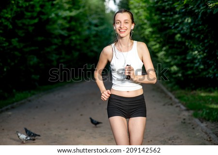 Running woman. Female runner jogging during outdoor workout in a park. Beautiful fit girl. Fitness model outdoors. Weight Loss. Healthy lifestyle. - stock photo