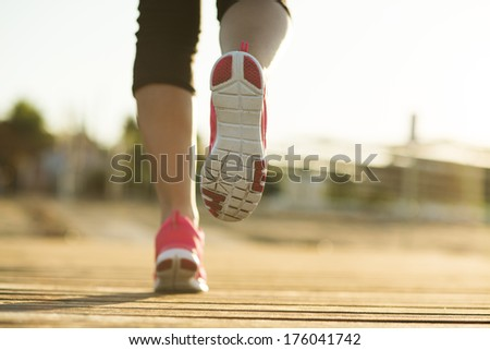 Running woman. Female runner jogging during outdoor workout on pier. Feet detail. - stock photo