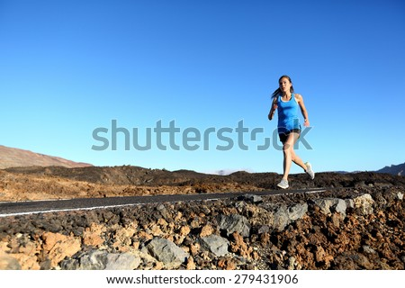 Running woman - female runner jogging outdoors on road training for marathon run as part of healthy lifestyle outdoor workout in summer. Mixed race Asian Caucasian model. - stock photo