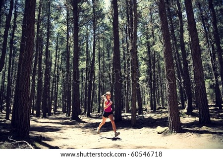 Running woman. Female runner running in forest. Beautiful Asian / Caucasian woman athlete jogging outdoors in beautiful forest with lots of mood / atmosphere and copy space. - stock photo
