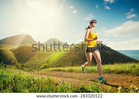 Running woman. Girl jogging on trail in mountains on field with grass in summer sunny day. Fitness. Healthy lifestyle.  - stock photo