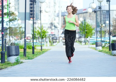 Running woman jogging in city street park at beautiful summer morning. Sport fitness model caucasian ethnicity training outdoor. - stock photo