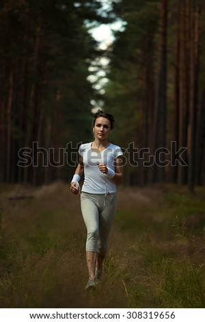 Running woman jogging in  in wooded forest area. Young lady running on forest trail in beautiful nature. Fitness healthy lifestyle concept with female athlete trail runner. - stock photo