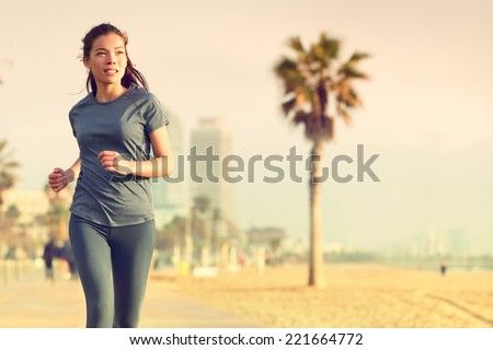 Running woman jogging on beach boardwalk. Healthy lifestyle girl runner training outside working out. Mixed race Asian Caucasian fitness woman exercising outdoors. - stock photo