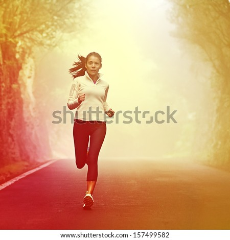 Running woman jogging on road in sunrise and mist. Female runner working out in fall or winter sports outfit. Beautiful multiracial Asian Caucasian woman athlete outside. - stock photo