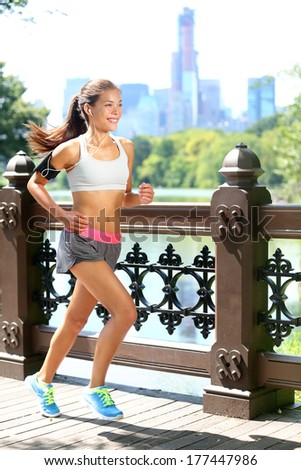 Running woman jogging to music in New York City, Central Park, Manhattan. Runner wearing earphones and armband for smart phone. Female fitness jogger training outside for healthy lifestyle. - stock photo